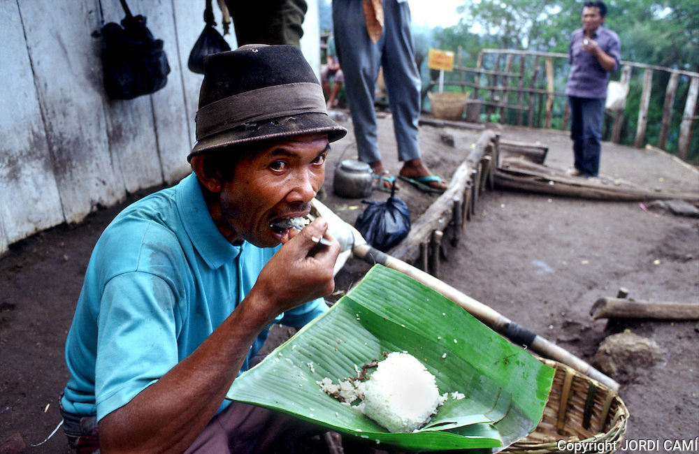 Miner eating out of the cantine placed to half of the way of decrease of the active crater of Volcano Kawa Ijen. Eastern Java, Indonesia