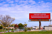 """14 OCTOBER 2020 - DES MOINES, IOWA: An electronic in front of the Des Moines airport welcomes people to the """"Trump COVID SuperSpreader Event."""" President Donald Trump has been criticized for his handling of the COVID-19 pandemic. The sign was paid for by Rural America 2020. Trump, who is recovering from COVID-19 is hosting a campaign event at the Des Moines airport.       PHOTO BY JACK KURTZ"""