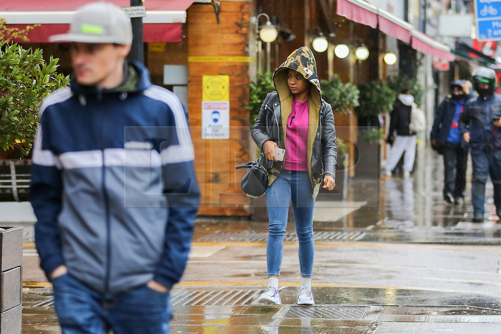 © Licensed to London News Pictures. 14/11/2020. London, UK. A woman is caught in the rain in north London. The Met Office has issued a yellow weather warning for the UK for heavy rain and strong winds, as up to 20 days worth of rain is expected to fall in the next few days. Photo credit: Dinendra Haria/LNP