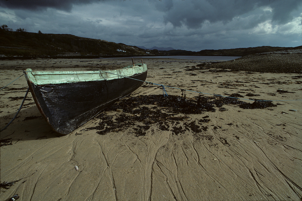 Ireland, County Galway, Clifden, Storm clouds over fishing skiff along lake shore on autumn afternoon