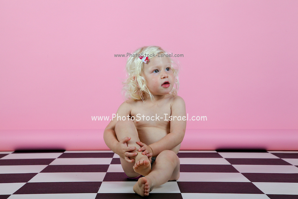 young blonde girl of two sits on a checkered floor Model release available