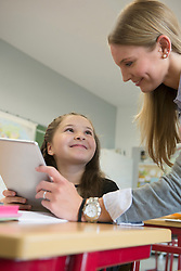 Female teacher showing a girl something on digital tablet pc in classroom, Munich, Bavaria, Germany