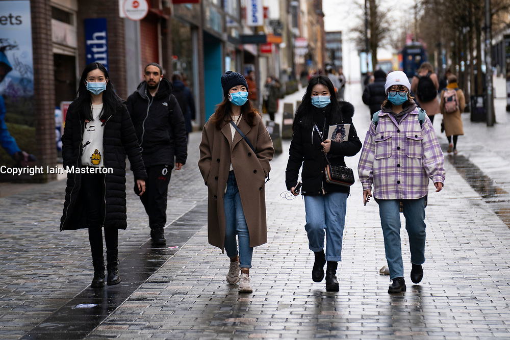 Glasgow, Scotland, UK. 12 March 2021. On the day Covid-19 lockdown is relaxed slightly in Scotland the city centre streets in Glasgow city centre remain almost deserted virtually all shops ad cafes are still closed. Pic; Chinese women wearing facemarks walk along a very quiet Sauchiehall Street. Iain Masterton/Alamy Live News