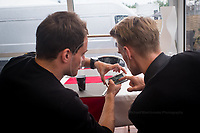 Oliver Webb (GBR) and Simon Trummer (SUI) looking at images of their car on fire last night. #4 LMP1 Bykolles Racing Team CLM P1/01 - AER discuss tactics over lunch 24hr Le Mans 16th June 2016
