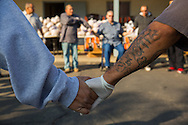 Sanger, CA.  Volunteers join hands for a prayer before distributing food to the local community.