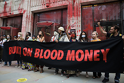 London, UK. 27th August, 2021. Environmental activists from Extinction Rebellion stand behind a banner outside the Guildhall after it was sprayed with blood-red paint during a Blood Money March through the City of London on the fifth day of Impossible Rebellion protests. Extinction Rebellion were intending to highlight financial institutions funding fossil fuel projects, especially in the Global South, as well as law firms and institutions which facilitate them, whilst calling on the UK government to cease all new fossil fuel investment with immediate effect.