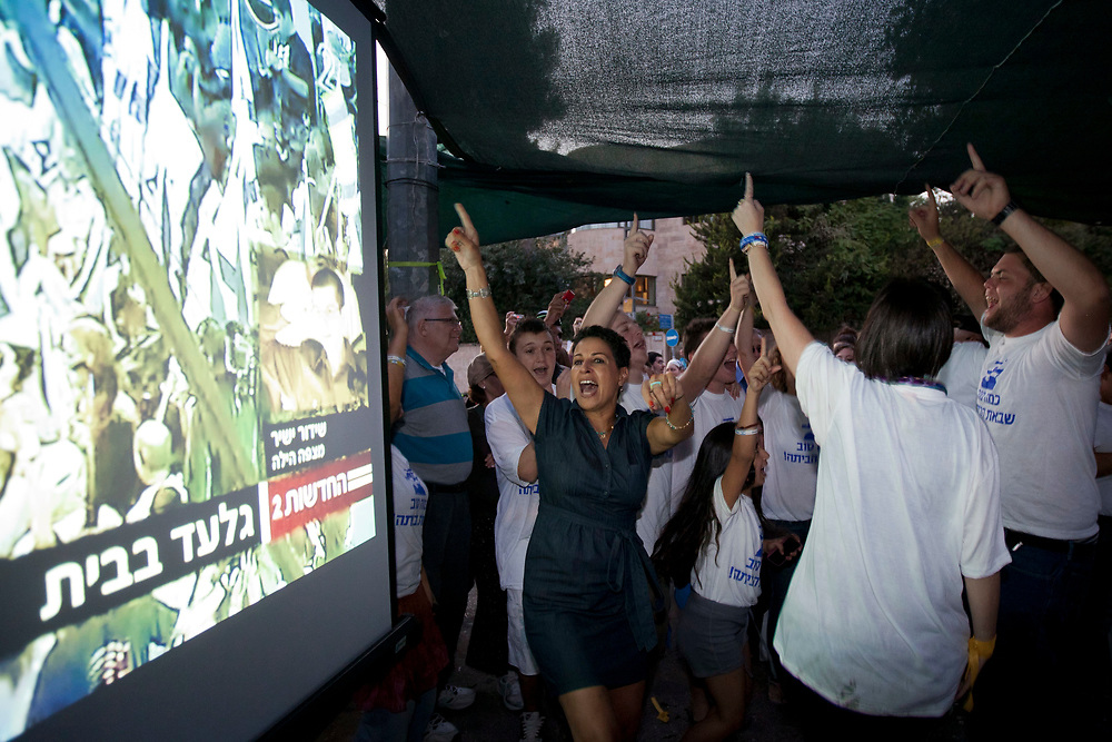 Israelis celebrate as they watch images of Israeli Defense Forces soldier Gilad Shalit on TV as he arrives at his home town of Mitzpe Hila on October 18, 2011 outside a protest tent set to call for his release, near Prime Minister Netanyahu's residence in Jerusalem, Israel. Shalit was freed after being held captive for five years in Gaza by Hamas militants, in a deal which saw Israel releasing more than 1,000 Palestinian prisoners.
