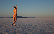 Photo of a nude woman posing on the Bonneville Salt Flats, Utah at sunset