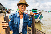 13 JUNE 2013 - YANGON, MYANMAR:  A porter waits for customers on a jetty in the Annawa Fish Market. The Annawa Fish Market in Yangon is one of the largest fish markets in Myanmar. It serves as both a wholesale and retail market and serves both exporters and domestic customers. With thousands of miles of riverine waterways and ocean coastline Myanmar has a large seafood and fishing industry.   PHOTO BY JACK KURTZ