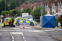 CAPTION UPDATE © Licensed to London News Pictures. 31/07/2021. High Wycombe, UK. Police vehicles form a cordon on Micklefield Road next to a large tent and forensic investigator as a murder investigation is launched in High Wycombe following the discovery by a police patrol of a person on the ground at approximately 12:20BST surrounded by a group of males who fled the scene when the police officers arrived, despite the efforts of police and paramedics the man died at the scene. Photo credit: Peter Manning/LNP