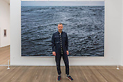 Tillmans with The State We are In, A 2015 - Wolfgang Tillmans: 2017. Tate Modern's new exhibition. Highlights include: large scale photographic works printed especially for this exhibition, including the four-meter tall Weed 2014 and dramatic seascapes such as The State We're In, A 2015;   New 'text and table' sculptures including Time Mirrored 3 2017, on display to the public for the first time; and slide projection Book for Architects 2014. The show is at Tate Modern from 15 February to 11 June 2017.