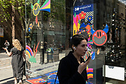 Woman speaking into her smartphone in Covent Garden district interacts with a brightly coloured window display for Sunglasses Hut on a street corner on 26th May 2021 in London, United Kingdom. Symbols of weather have been painted onto the windows depicting rainbows, lightening strikes, clouds and rain drops.