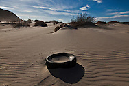 An old car tire in the sands of the Mojave desert near Barstow, CA.<br /> U.S. Route 66, also known as the Mother Road, in the Mojave desert of California. The two major connector cites in the Mojave desert are Barstow and Amboy. U.S. Route 66 was the first major east west highway for the US, starting in Chicago, Il and ending in Santa Monica, CA. The 2,448 mile long highway was built in November 11,1926. Most of Route 66 has been decommissioned, but there are several parts that are now historically preserved.