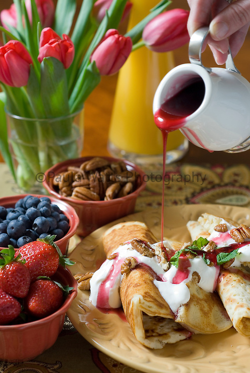French crepes for breakfast spread with berry syrup