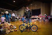 Roberto Ramirez poses for a portrait with a bike he received for his son during a Milpitas Fire Department toy drive at Genesis United Methodist Church in Milpitas, California, on December 21, 2013. (Stan Olszewski/SOSKIphoto)