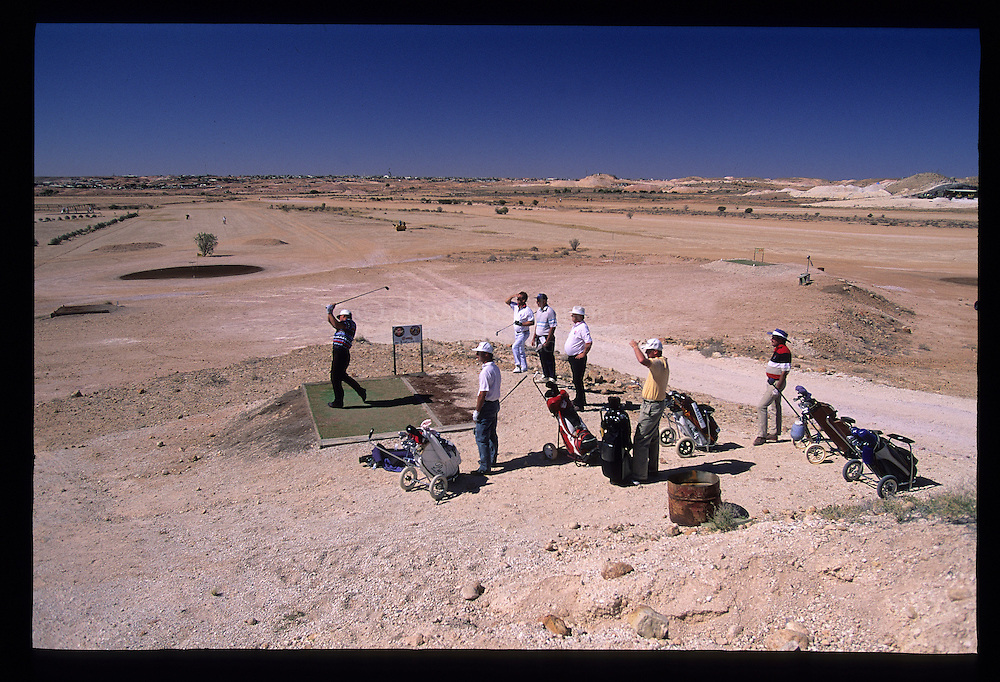 COOBER PEDY, AUSTRALIA:  Golfing in the desert in Coober Pedy, Australia. The opal mining town in central Australia is known for it's underground homes and quirky events such as the Easter Golf Tournament played out over a desert golf course and dirt road racing. Photograph by David Paul Morris