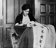 Alice Paul, half-length portrait, seated, sewing suffrage flag. Between 1912 and 1920.