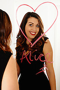 Portrait of Alice reflected in a mirror. She has written her name and a large heart on it in lipstick. She is smiling happily at the camera. Image was taken in a Bristol apartment by Jonathan Bowcott