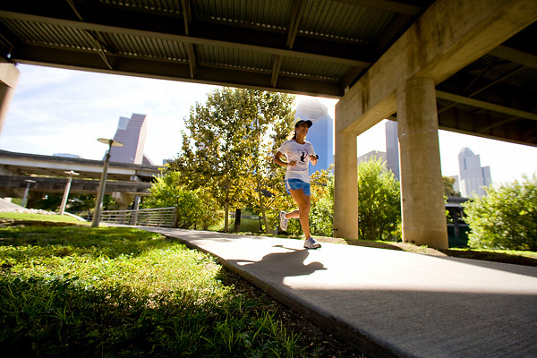 Woman jogging on a pathway under an overpass in Buffalo Bayou park in Houston, Texas