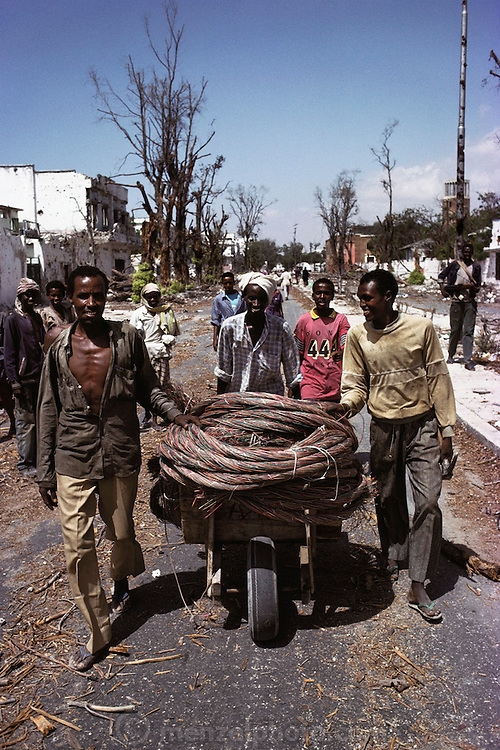 Men looting copper phone wires. The scrap copper sells for $1.25 a kilo. This photo was taken at the front lines on the north side of Mogadishu, the war-torn capital of Somalia. March 1992.