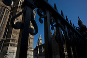The tower containing Big Ben amid the Gothic architecture of Britain's Houses of Parliament seen through railings.