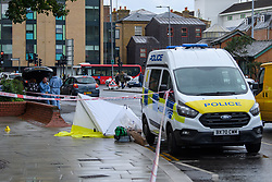 © Licensed to London News Pictures. 21/08/2021. London, UK. A police vehicle and forensic tent at the scene of a fatal stabbing in Kingston. Police were called to a disturbance on Clarence Street at 03:45BST where they found a 22-year-old male with a stab injury to the chest, he was taken to hospital by London Ambulance Service where he was pronounced dead. An 18-year-old male was arrested at the scene on suspicion of murder.Photo credit: Peter Manning/LNP
