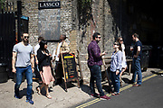 People hanging out at Maltby Street food market in London, England, United Kingdom. Maltby Street is an artisan food market under the railway arches in Bermondsey.