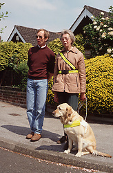 Woman with visual impairment standing on pavement with dog trainer and guide dog preparing to cross road,