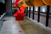 A child lays on the floor beneath the textiles and language-themed sculpture entitled 'I Don't Know. The Weave of Textile Language' by American artist Richard Tuttle in Tate Modern's Turbine Hall. Tate Modern's Turbine Hall has played host to some of the world's most striking and memorable works of contemporary art. Now, this vast space welcomes the largest work ever created by renowned American sculptor Richard Tuttle (born 1941).  this newly commissioned sculpture combines vast swathes of fabrics designed by the artist from both man-made and natural fibres in three bold and brilliant colours.