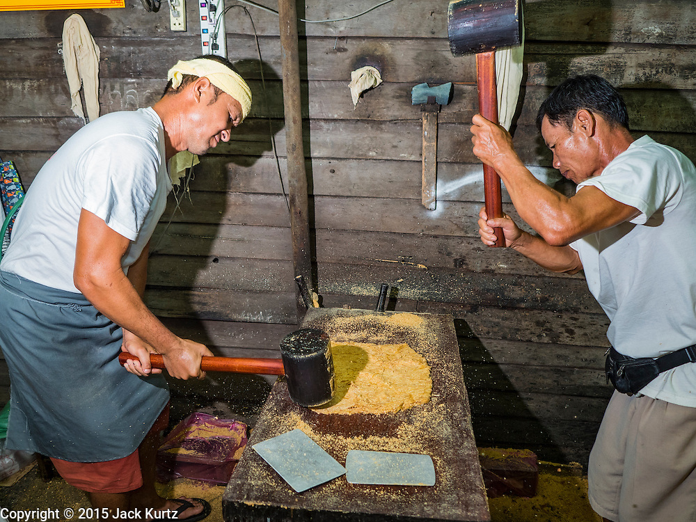15 OCTOBER 2015 - BANGKOK, THAILAND:  Thai candy makers use mallets to make peanut brittle like snacks during the Vegetarian Festival at the Joe Sue Kung Shrine in the Talat Noi neighborhood of Bangkok. The Vegetarian Festival is celebrated throughout Thailand. It is the Thai version of the The Nine Emperor Gods Festival, a nine-day Taoist celebration beginning on the eve of 9th lunar month of the Chinese calendar. During a period of nine days, those who are participating in the festival dress all in white and abstain from eating meat, poultry, seafood, and dairy products. Vendors and proprietors of restaurants indicate that vegetarian food is for sale by putting a yellow flag out with Thai characters for meatless written on it in red.   PHOTO BY JACK KURTZ