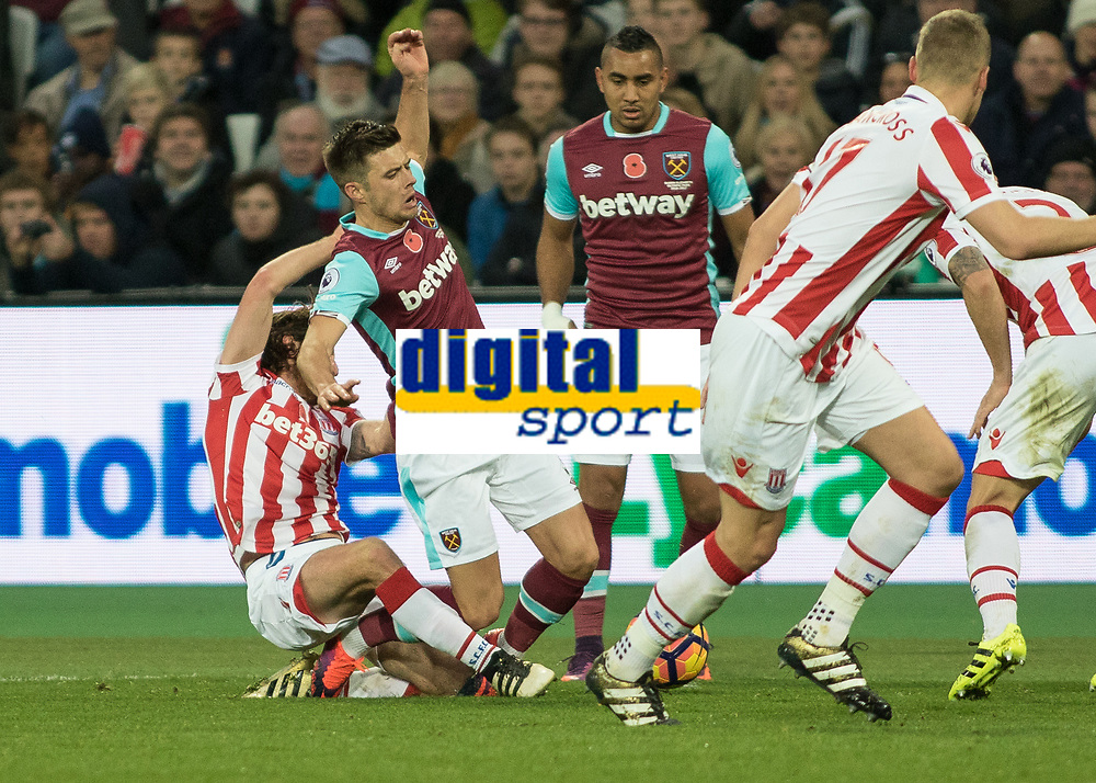 Football - 2016 / 2017 Premier League - West Ham United vs. Stoke City<br /> <br /> Joe Allen of Stoke City takes down Aaron Cresswell of West Ham from behind at The London Stadium.<br /> <br /> COLORSPORT/DANIEL BEARHAM
