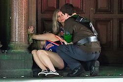 © Licensed to London News Pictures . 27/12/2017. Wigan, UK. A man and a woman tend to a woman who is slumped over in a doorway. Revellers in Wigan enjoy Boxing Day drinks and clubbing in Wigan Wallgate . In recent years a tradition has been established in which people go out wearing fancy-dress costumes on Boxing Day night . Photo credit: Joel Goodman/LNP