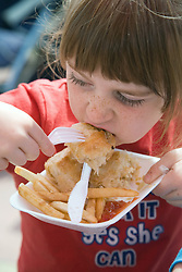 Young girl tucking into some fish and chips,