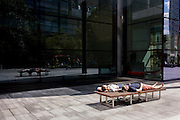 Two men sleep in summer sunshine, sharing a bench in the pedestrian area of Spitalfields in central London.