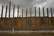 Granjeno, TX - 4 Sep 2008 -<br /> A construction worker walks above the border wall under construction along the Rio Grande in Granjeno as rain clouds roll in.