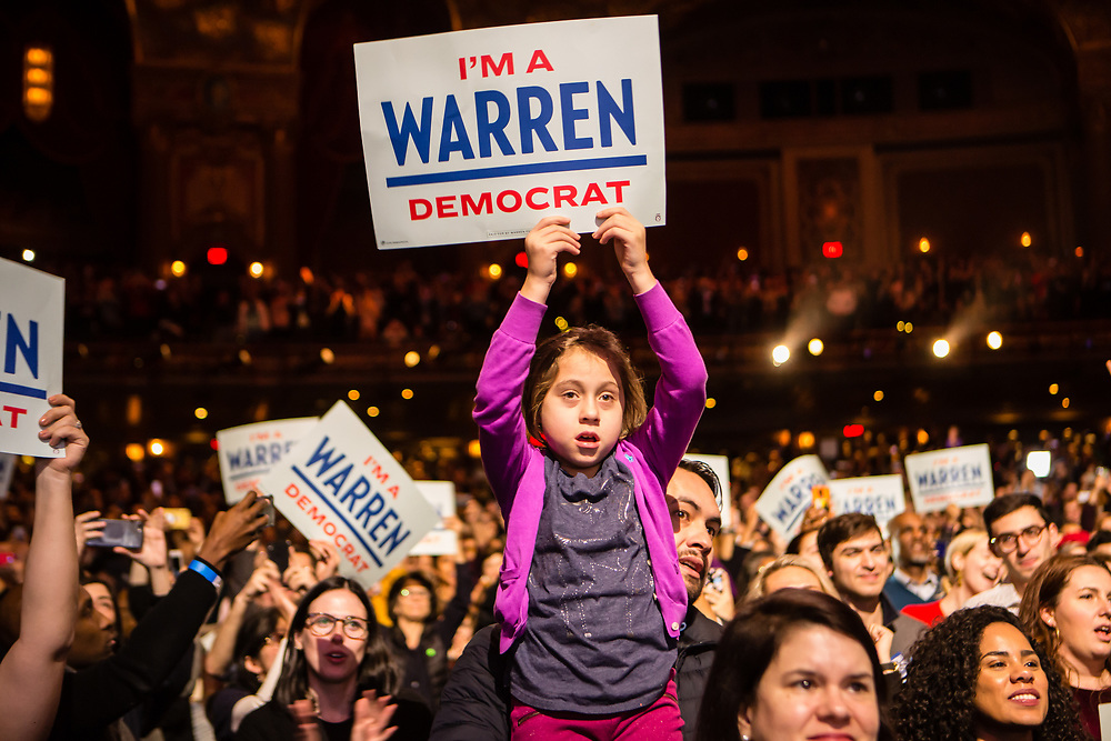 "Brooklyn, NY - 7 January 2020. Massachusetts Senator and Democratic Presidential candidate Elizabeth Warren, joined by former candidate Julián Castro, drew a large and enthusiastic crowd at a speech for her 2020 presidential campaign in Brooklyn's Kings Theatre. A young girl holds a sign reading ""I'm a Warren Democrat."""