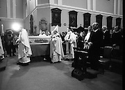 Funeral Of Frank Duff.   (N50)..1980..13.11.1980..11.13.1980..13th November 1980..The Solemn Funeral Mass for Frank Duff, founder of The Legion of Mary,was concelebrated with his Eminence,Cardinal Tómas O'Fiaich,Archbishop of Armagh and Primate of All Ireland as principal celebrant, at St Andrew's Church, Westland Row,Dublin. The funeral took place after the mass to Glasnevin Cemetery..The coffin containing the mortal remains of Frank Duff lie in state in St Andrew's Church. Image shows Cardinal O'Fiaich passing the coffin,President Patrick Hillery and Mr Michael Woods are pictured on the right.