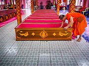 "29 MARCH 2017 - BANG KRUAI, NONTHABURI, THAILAND:  A Buddhist monk picks up money left in a coffin as a donation after a ""Resurrection Ceremony"" at Wat Ta Kien (also spelled Wat Tahkian), a Buddhist temple in the suburbs of Bangkok. People go to the temple to participate in a ""Resurrection Ceremony."" Groups of people meet and pray with the temple's Buddhist monks. Then they lie in coffins, the monks pull a pink sheet over them, symbolizing their ritualistic death. The sheet is then pulled back, and people sit up in the coffin, symbolizing their ritualist rebirth. The ceremony is supposed to expunge bad karma and bad luck from a person's life and also get people used to the idea of the inevitability of death. Most times, one person lays in one coffin, but there is family sized coffin that can accommodate up to six people. The temple has been doing the resurrection ceremonies for about nine years.         PHOTO BY JACK KURTZ"