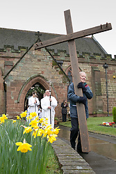 "© Licensed to London News Pictures. 3/4/2015. Solihull, West Midlands, UK. The Good Friday ""Walk of Witness"" taking place in Solihull. People of all faiths congrgate outside St Alphege Church and walk the short distance to Mell Square to hold a multi-faith prayer meeting. Pictured, The cross begins it's journey through Solihull. Photo credit : Dave Warren/LNP"