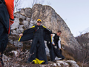 BASE-jumpers preparing wingsuits for launch, Monte Brento, Italy