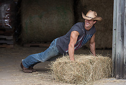 hot cowboy doing a pushup on a hay bale in a barn