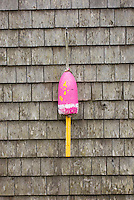 Colorful lobster buoys hanging on shingle wall of fishermans shack Bristol Maine, USA