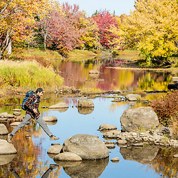 A man crosses Mud Brook, a tributary of the East Branch of the Penobscot River in Maine's Northern Forest. Fall.