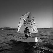 Elève apprenant à naviguer dans un petit voilier (optimiste) sur le lac de Morat. Junger Segler im Optimisten auf dem Murtensee. © Romano P. Riedo