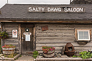 Famous Salty Dawg Saloon in the original log cabin built in 1897 along the marsh boardwalk on Homer Spit on Kamishak Bay in Homer, Alaska.