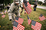 10 SEPTEMBER 2020 - DES MOINES, IOWA: A US Air Force Airman sets out American flags in Des Moines. About 25 volunteers braved cold and rainy weather Thursday to line the west end of Gray's Lake in Des Moines with American flags. The display of the flags was a part of an annual event called the 9/11 Tribute Trail. About 3,000 flags were set out in memorial of the 3,000 people killed in the 9/11 terrorist attacks.     PHOTO BY JACK KURTZ