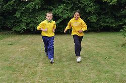 Two children running outside,