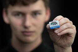 """© Licensed to London News Pictures . 22/04/2020. Manchester, UK. In an echo of Health Secretary Matt Hancock's pose with a """"CARE"""" badge , Porter LEWIS MACLENNAN (21) , holds a commemorative badge , being given as a gift to those who have worked at the NHS Nightingale Hospital in Manchester . The National Health Service has built a 648 bed field hospital for the treatment of Covid-19 patients , at the historical railway station terminus which now forms the main hall of the Manchester Central Convention Centre . The facility is treating patients from across the North West of England , providing them with general medical care and oxygen therapy after discharge from Intensive Care Units . Photo credit : Joel Goodman/LNP"""