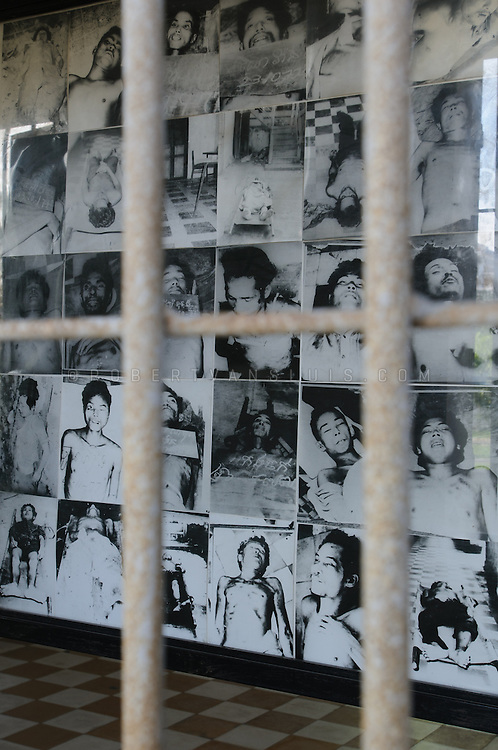 Bar fence and portraits of deceased prisoners at Tuol Sleng Museum of Genocide, Cambodia
