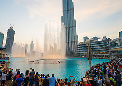Crowds of people watch dancing fountains on pond outside Dubai Mall in Dubai, UAE